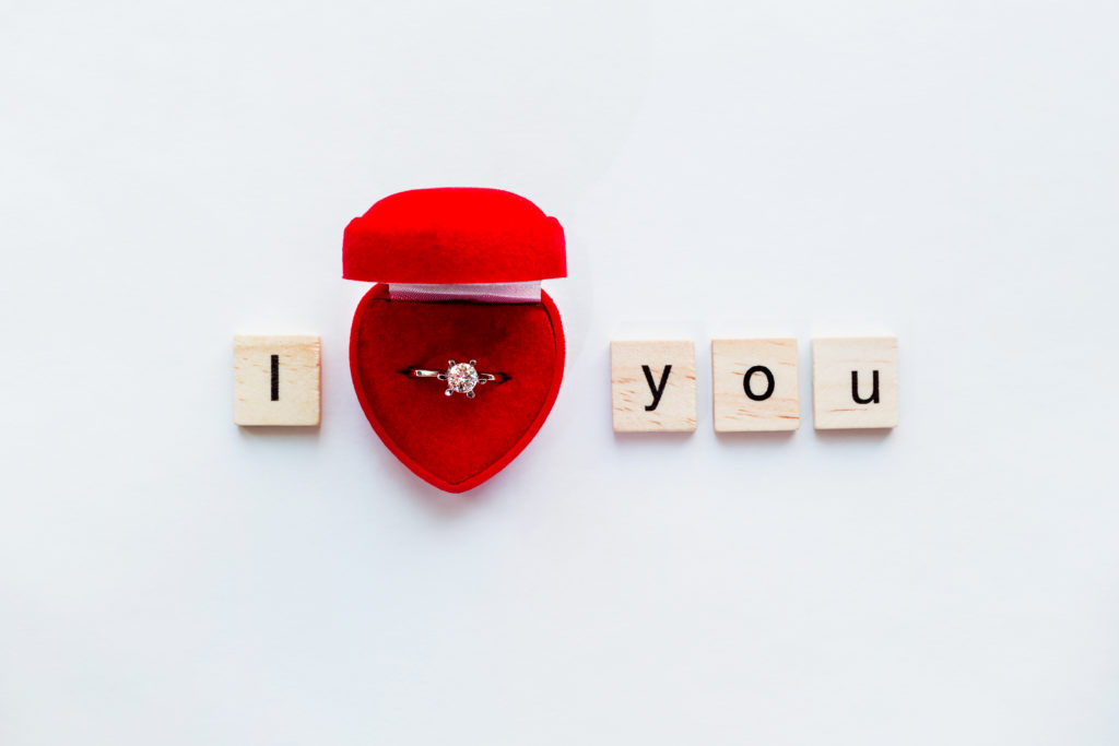 Diamant Ring Hochzeit Ich liebe dich White background with wooden words I LOVE YOU and diamond engagement ring in red gift box. Good as card or background for Valentine's Day of engagement card.